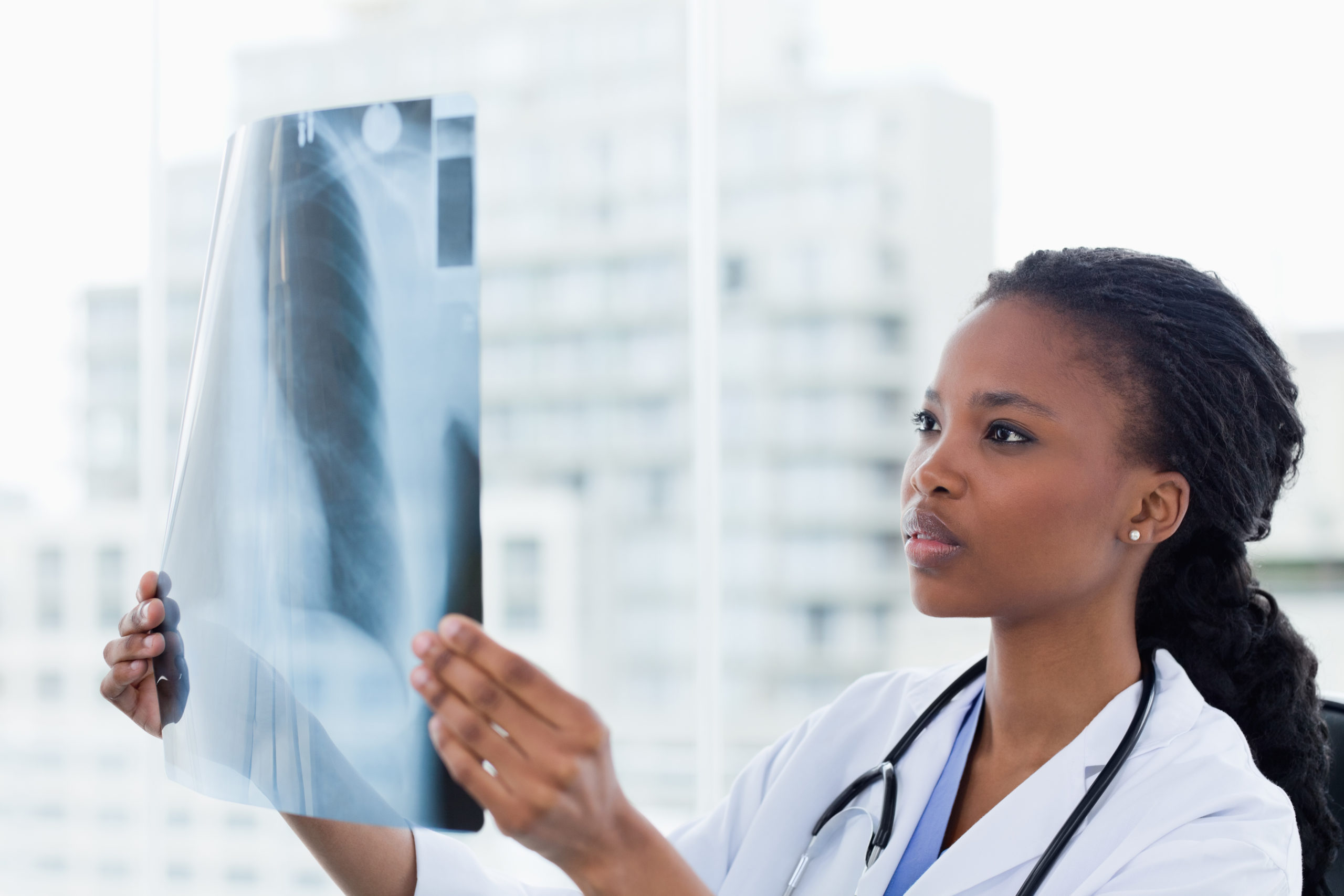 Female doctor looking at a set of X-rays in her office